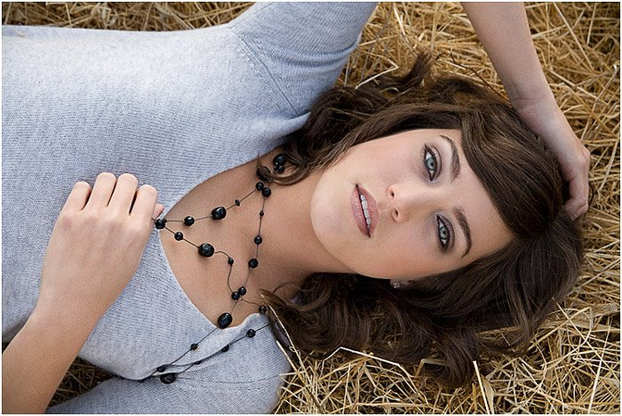 Overhead photo of a beautiful female model lying on straw