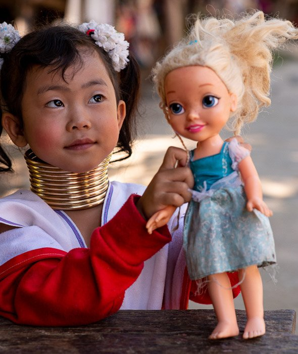 A young karen girl holding a plastic doll
