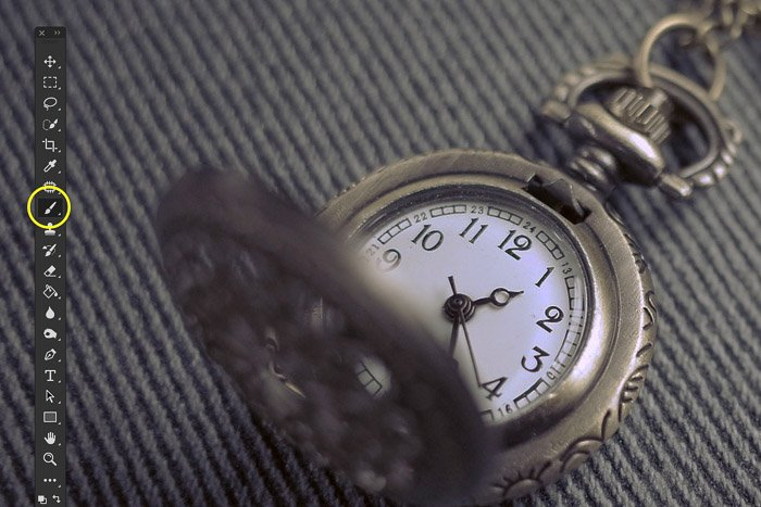 A close up product photography shot of a pocket watch edited with clone stamp tool