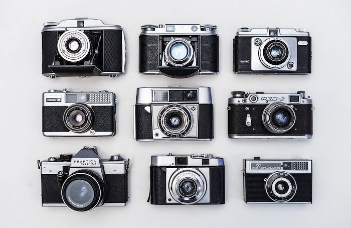 A flat lay of nine old film cameras on a white background - professional photo shoot