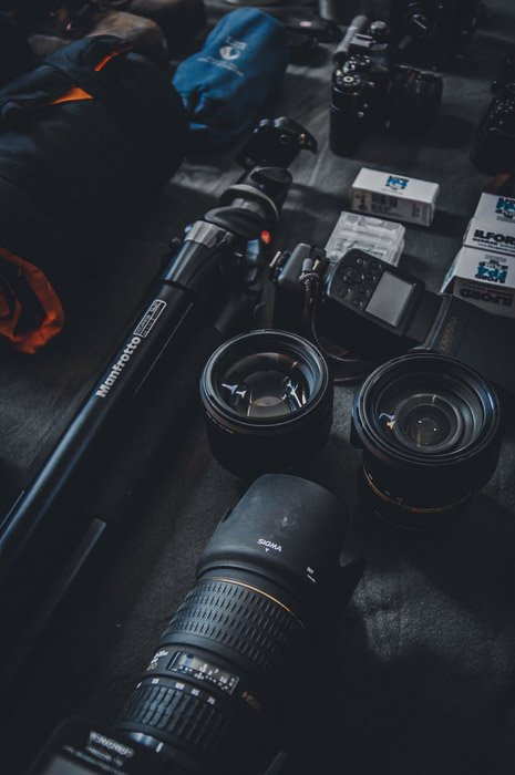 Camera lenses, tripod and other photography equipment of a black table