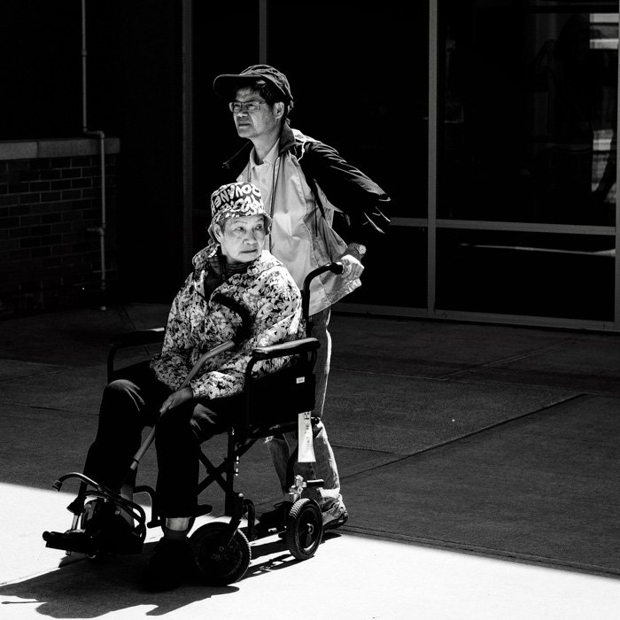 A black and white portrait of a man pushing a lady in a wheelchair outdoors, shot using pull film processing