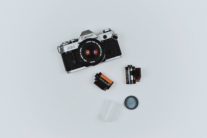 A flat lay of a canon film camera and film rolls on white background - how to pull or push film