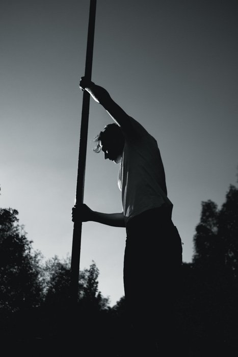 A black and white portrait of a man holding a large pole - push film processing