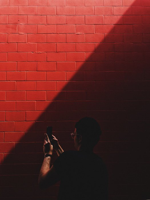 A man taking a smartphone photo of a red brick wall - push film processing