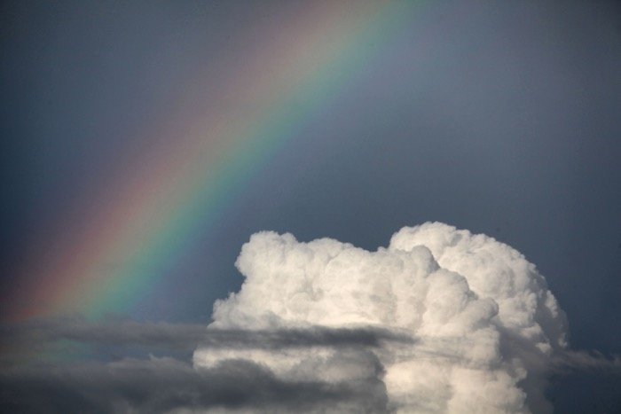 A stunning rainbow picture beside a white fluffy cloud