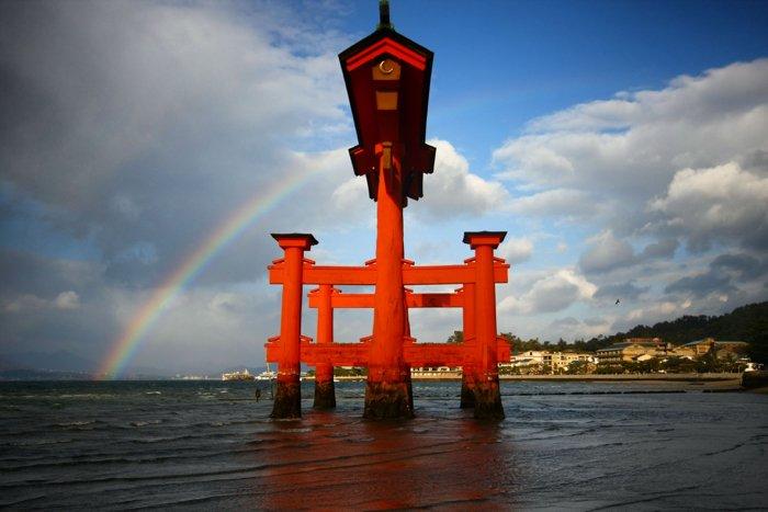 A stunning rainbow behind the famous gate on Miyajima island in Japan.