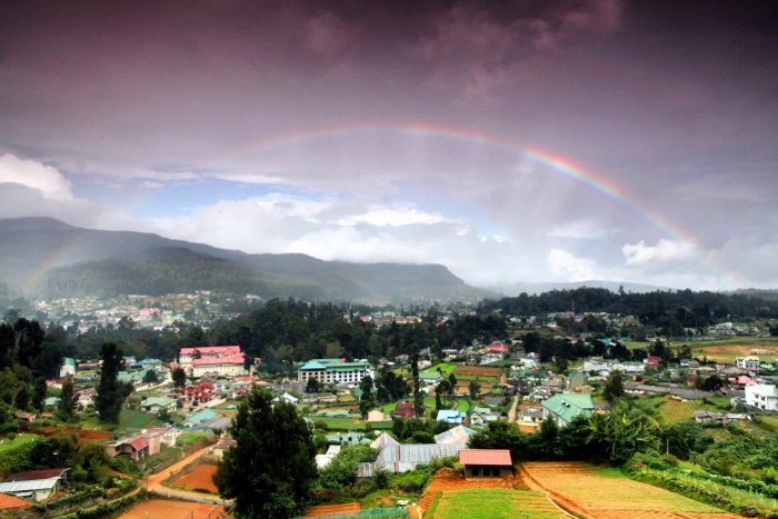 A beautiful landscape with a full bow of the rainbow above - rainbow photography tips