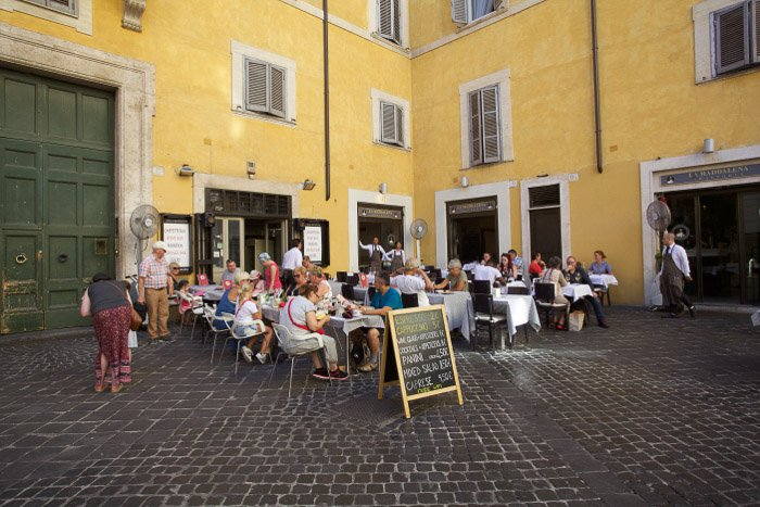 A crowded outdoor restaurant in rome - best rome photography spots