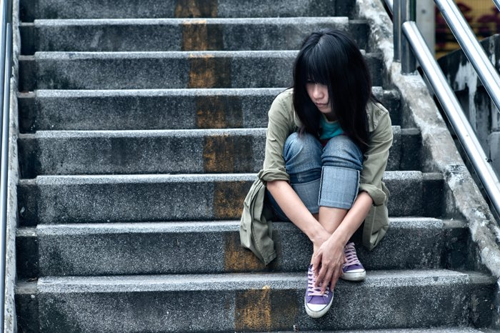A stock photography portrait of a female model sitting on stone steps