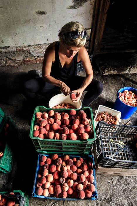 A portrait of a woman cutting fruit on the street