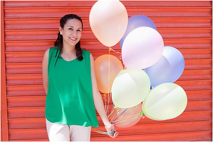 A female model posing with balloons in front of a red door - how to take pictures of people