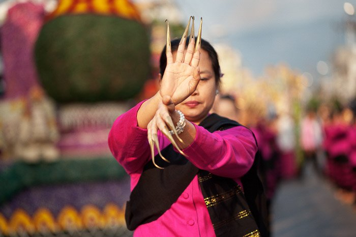 A photo of a Thai woman dancing in a street parade