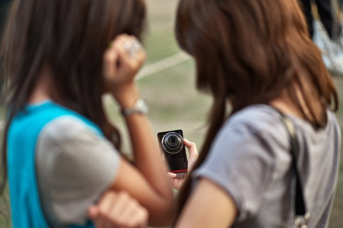 Two girls taking a selfie with a camera - shallow vs deep depth of field
