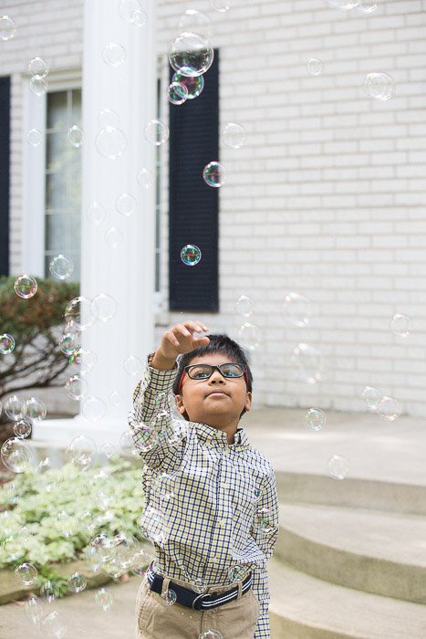 Outdoor portarit of a young boy playing with bubbles