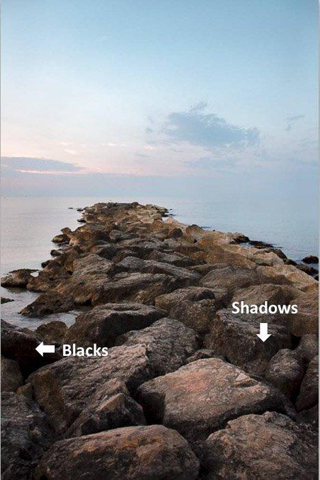 与指向阴影和黑色的箭头的一个惊人的沿海风景在岩石