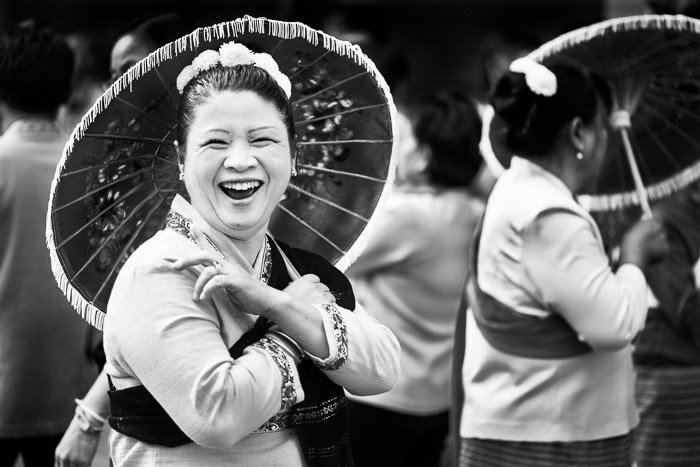 A black and white street portrait of a woman with an umbrella laughing with friends before the start of the annual flower parade. Narrative photography tips
