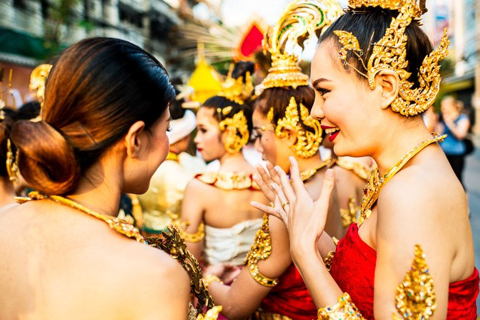 A street portrait of girls talking together while they wait for the flower parade they are taking part in to start. narrative photography ideas
