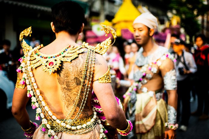 Dressed in a traditional costume a young man waits for the flower parade to start in Chiang Mai, Thailand. Narrative photography