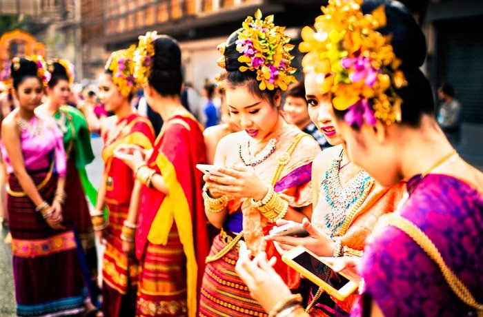 A street portrait of girls checking their smartphones before the start of the annual flower parade in Chiang Mai, Thailand. Photos that tell a story