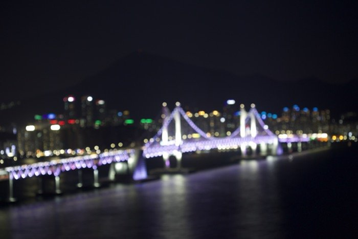 A blurry out of focus image of an illuminated bridge over a city river at night