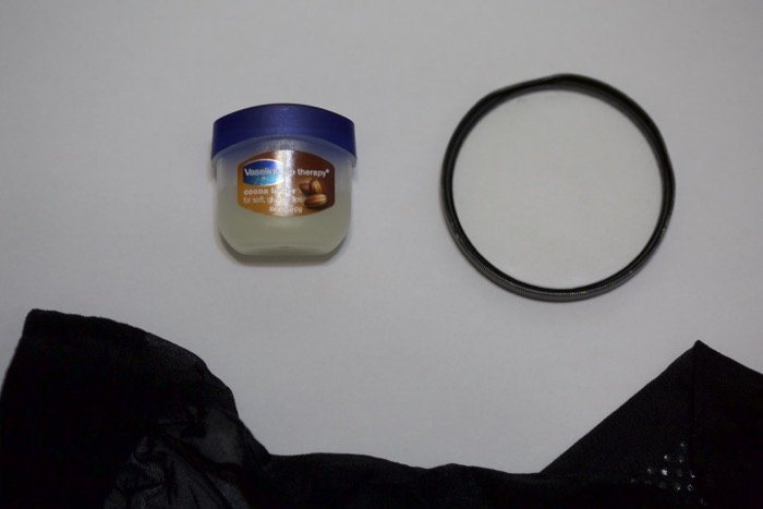 A flat lay of vaseline, lens filter and black stocking on white background - soft focus photography