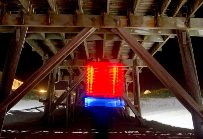 Blue and red light painting shot under a wooden structure at night using LED light painting tools