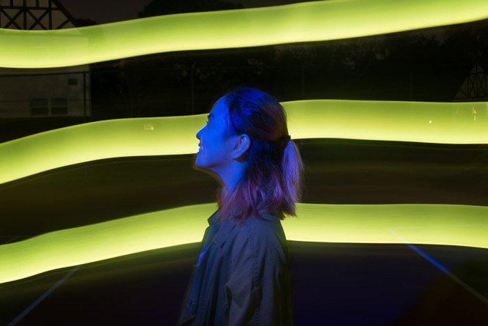 A portrait of a female model posing in from of neon green streaks of light