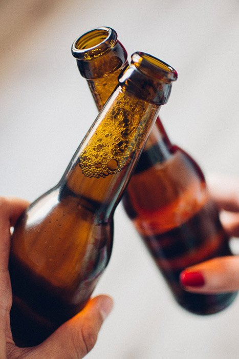 Beer photography shot of two people clinking glasses indoors
