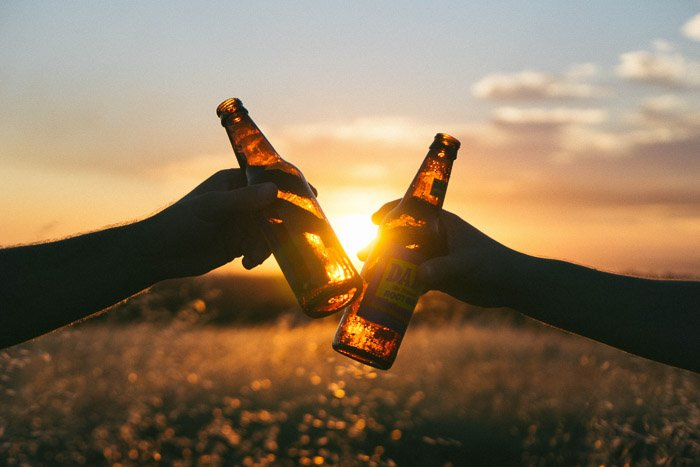 An outdoor beer photography shot of two people clinking bottles at sunset