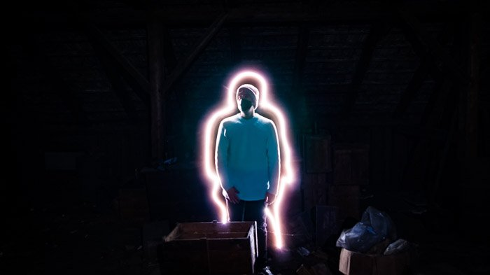 A creative portarit of a man with a line of light painting surroundeing him, shot using LED light painting tools