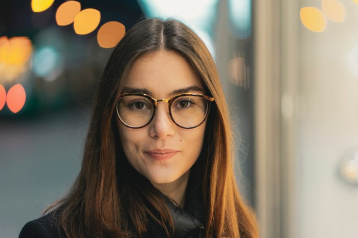 A portrait of a female model in glasses with a blurry bokeh background