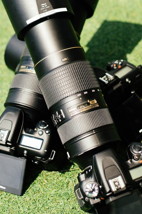 A photo of two DSLR camera with zoom lenses, outdoors on grass