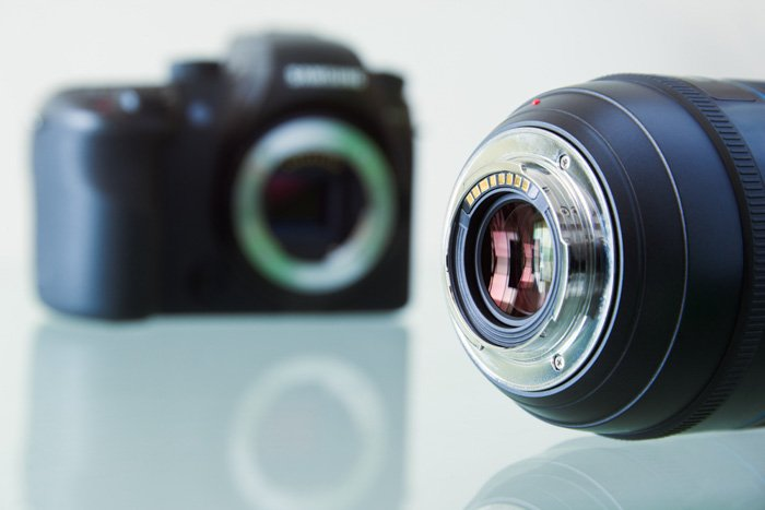 A camera lens in the foreground of a blurry dslr camera body