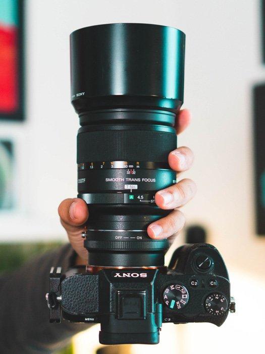 A person holding a DSLR camera - camera lens guide