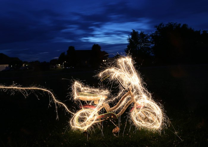 A bicycle surrrounded by light painting, outdoors at night, shot using LED light painting tools