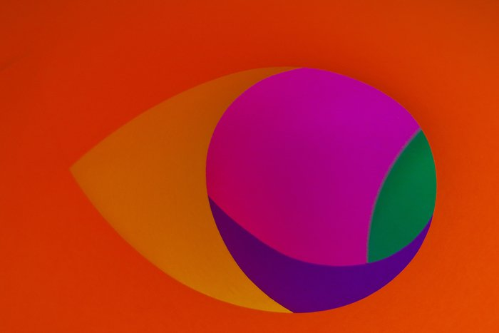 A creative abstract photo using 5 sheets of coloured paper - magenta, yellow, green, and purple sheets are rolled to look like circles