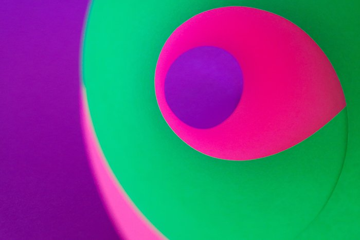 fun colorful abstract photo made using sheets of bright green, pink and purple colored paper