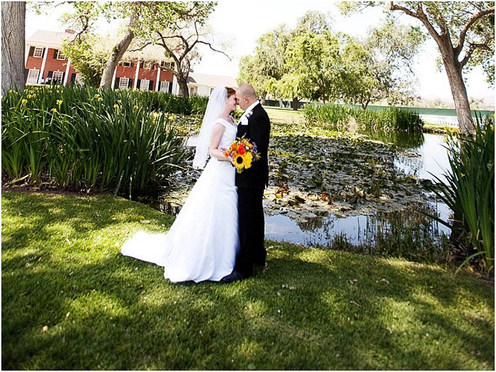 A newlywed couple posing outdoors in dappled light