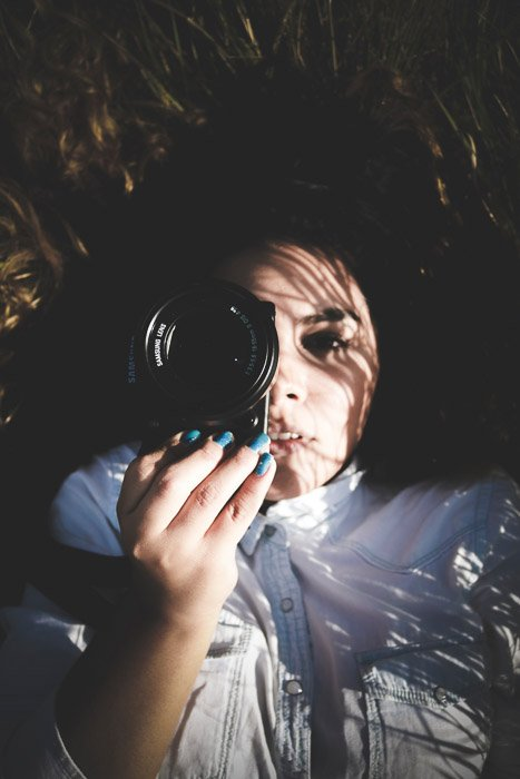 Atmospheric portrait of a female photographer lying on her back