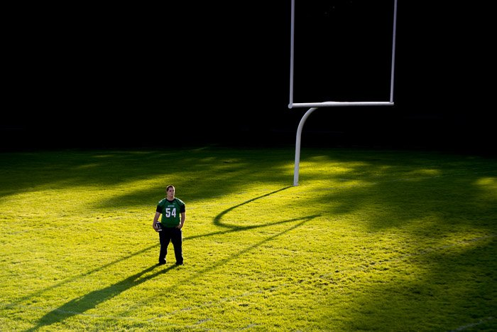 photo of a guy standing in the middle of a football pitch with dramatic lighting