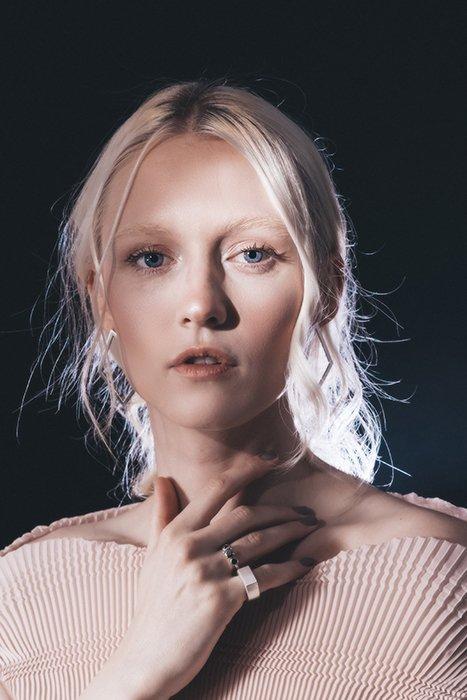 Dreamy backlit portrait of a female model posing against a black background