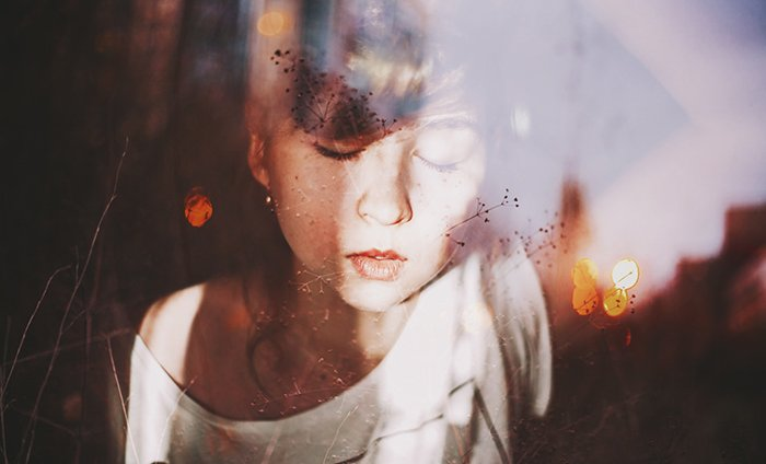 Dreamy portrait of a female model posing against a reflective surface - ethereal photos