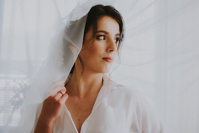 Dreamy portrait of a female model posing indoors with a white veil