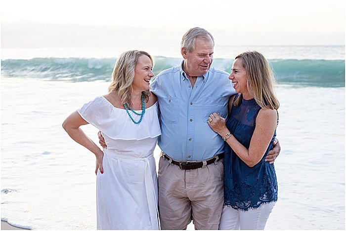 A sweet portrait of a family of three posing on the beach - emotional photography