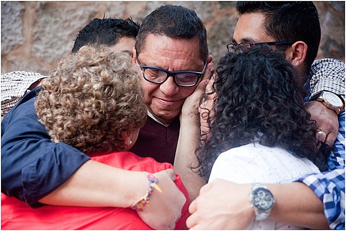 A candid portrait of a family in a group huddle - emotional photography