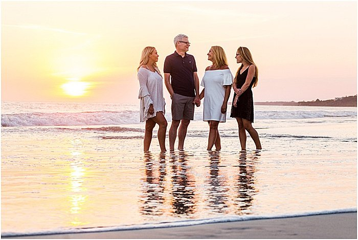 Asweet portrait of a family of four posing on the beach at sunset- emotional photography