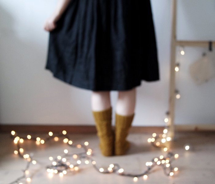 blurry indoor portrait of a female model standing in front of a string of lights - fairy light photography