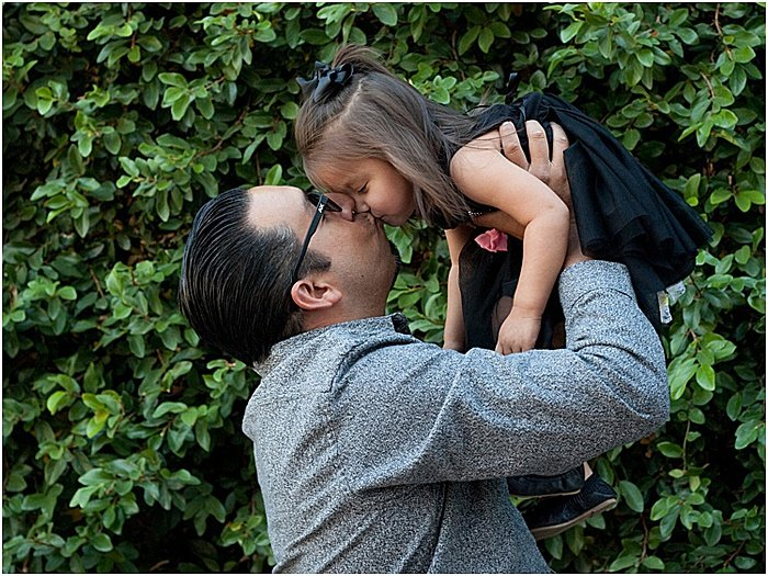 A sweet family portrait of a father and daughter playing outdoors