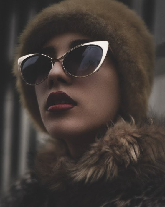 A beauty editorial fashion shot of a female model posing in sunglasses and fur - fashion photography types
